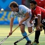 El argentino Lucas Rossi y el canadiense Sukhwinder Singh luchan por el balón en el partido por la medalla de oro del hockey. (Foto: AP/Terra Deportes)