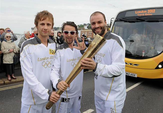 Dominic Howard, Matthew Bellamy y Christopher Wolstenholme sosteniendo la antorcha olímpica durante uno de los recorridos.