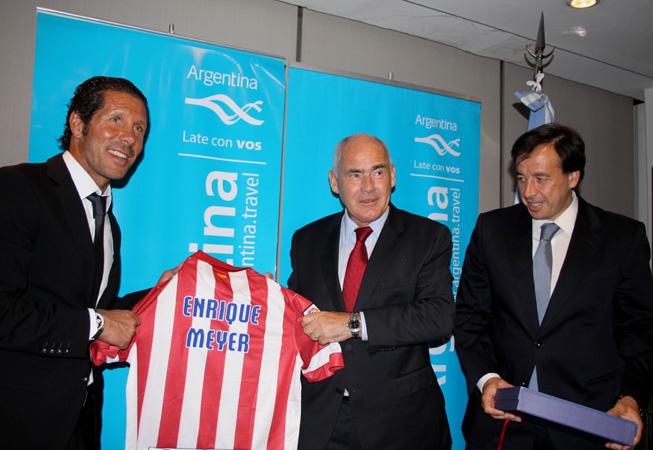 El director Técnico del Atlético Madrid, Diego Simeone, entrega la camiseta del club al ministro de Turismo de la Nación, Enrique Meyer, junto al vicepresidente de la institución española, Antonio Alonso.